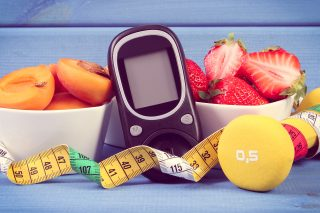 Vintage photo, Glucose meter for measuring sugar level, fresh healthy fruits, dumbbells for fitness and tape measure, concept of diabetes, slimming, healthy lifestyle